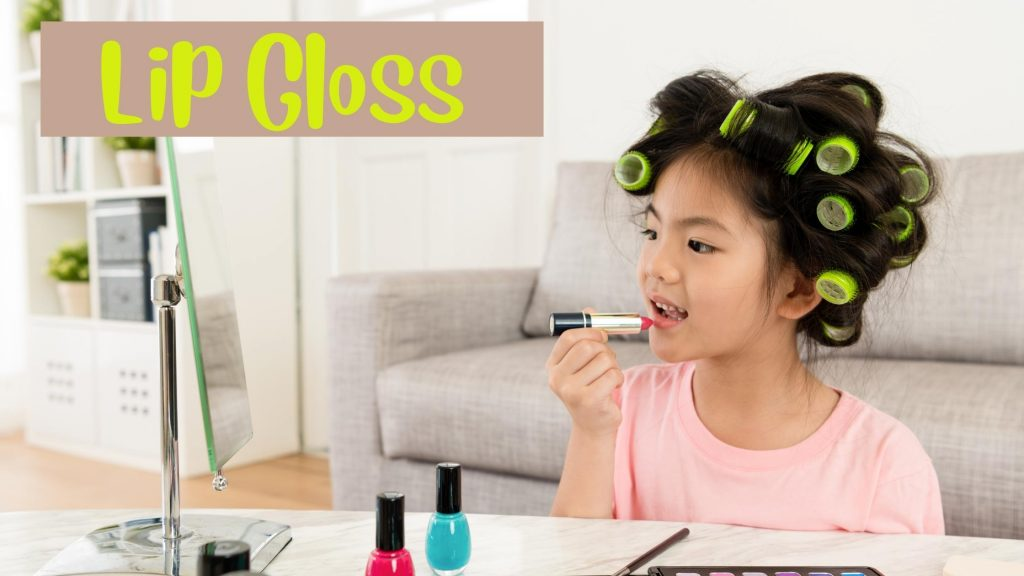 Little girl putting on lip gloss