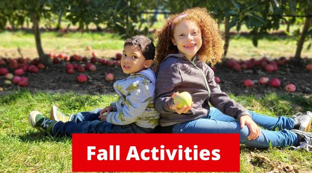 kids sitting in an apple orchard